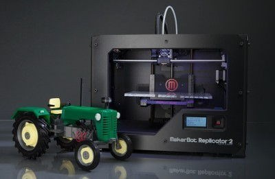 3D printed tractor model in front of Makerbot Replicator 2 3D printer