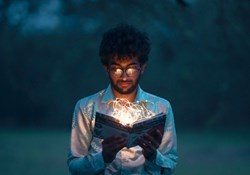 eliminating data bias: a person peers into a book with glowing coils coming out of it