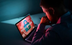 Ransomware: a concerned looking person sits in front of a computer screen with a red lock displayed